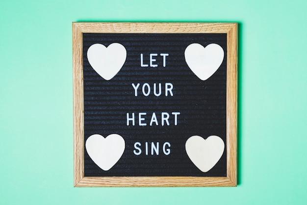 Placa decorada com mensagem e forma de coração no pano de fundo turquesa
