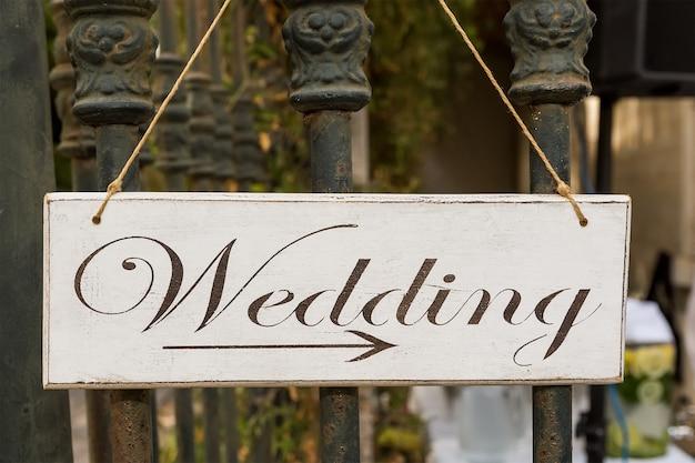 Placa decorativa com o casamento de inscrição. mostra a direção.