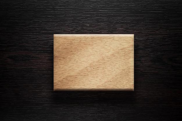 Placa em branco de madeira sobre fundo marrom escuro.