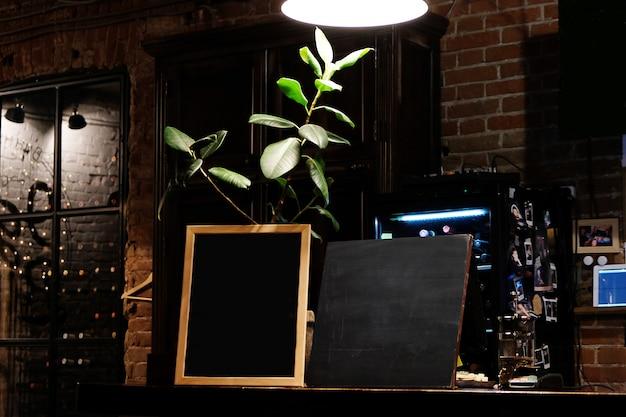 Placa em branco do menu sobre o fundo do café do borrão. lousa em branco no interior do pub