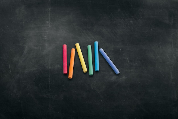 Placa escura com giz de cera colorido para desenhar fundo