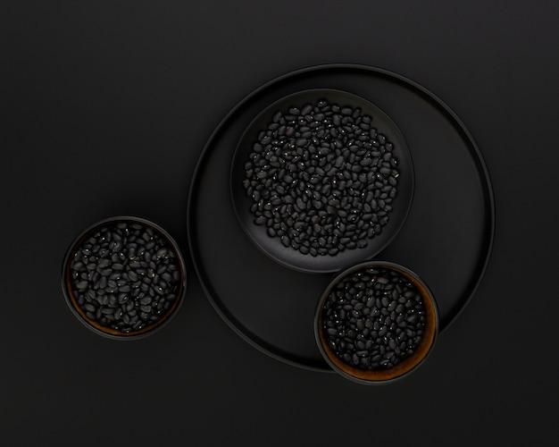 Placa escura com tigelas pretas de feijão em um fundo preto