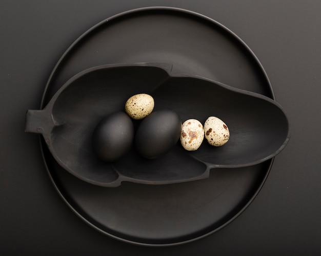 Placa escura em forma de folha com ovos em um prato escuro