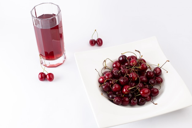 Placa frontal com cerejas azedas e maduras, juntamente com suco de cereja no branco