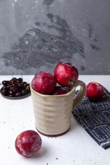 Placa frontal com cerejas escuras frescas azedas e maduras com ameixas frescas em cinza