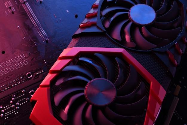 Placa gráfica de jogo de computador, placa de vídeo com dois coolers na placa de circuito, plano de fundo da placa-mãe. fechar-se. com iluminação vermelho-azulada.