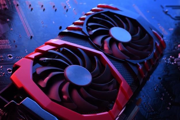 Placa gráfica do jogo de computador, placa de vídeo com dois coolers na placa de circuito, placa-mãe. fechar-se. com iluminação vermelho-azul