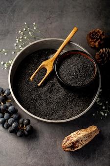 Placa metálica cinza cheia de sementes de papoila e uvas em um fundo cinza