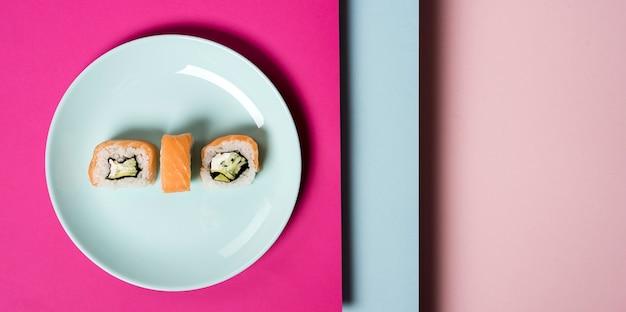 Placa minimalista com rolos de sushi e camadas de fundo