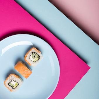 Placa minimalista com vista superior de rolos de sushi