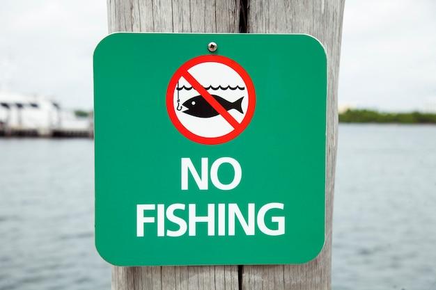 Placa na frente de um pouco de água pedindo às pessoas para não pescar nenhuma pesca além deste ponto.