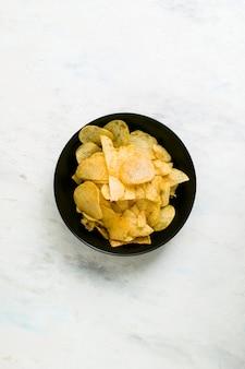 Placa preta cheia de batatas fritas em um fundo branco de madeira