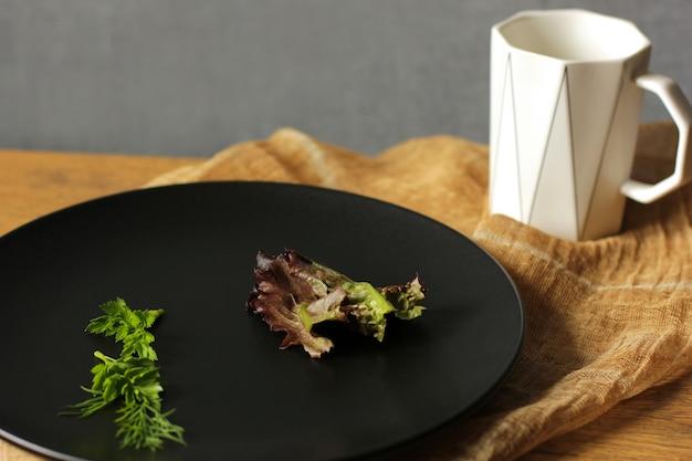 Placa preta com alface e uma xícara branca