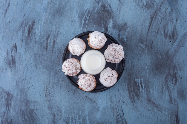 Placa preta com cupcakes cremosos doces e copo de leite na superfície de mármore.