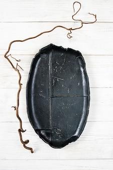 Placa preta com decoração de videira na mesa de madeira