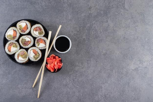 Placa preta com rolos de sushi colocados sobre fundo de pedra.