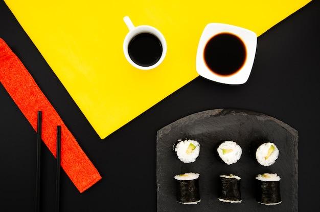 Placa preta com sushi e molho de soja em um fundo preto