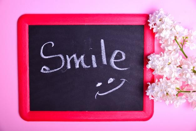 Placa preta com um sorriso de inscrição