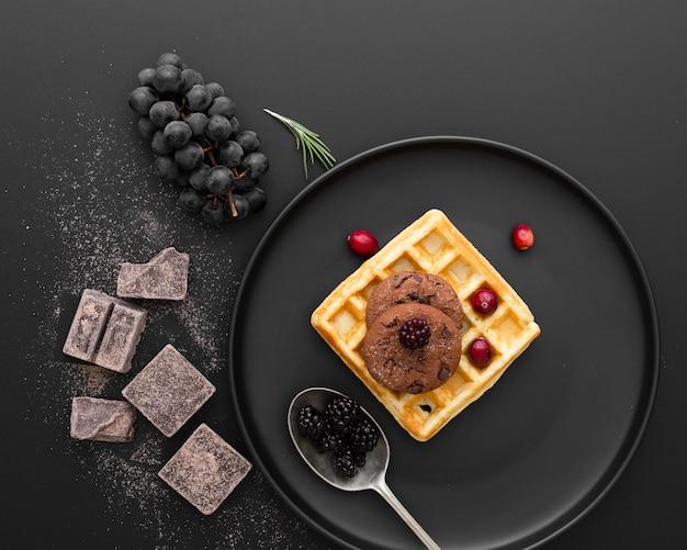 Placa preta com waffles em um fundo escuro com chocolate e uvas