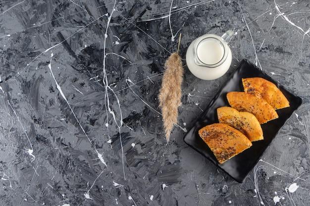 Placa preta de bolos frescos fatiados e copo de leite na mesa de mármore.