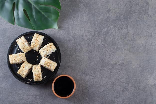 Placa preta de deliciosos rolos de sushi com sementes de gergelim na superfície da pedra