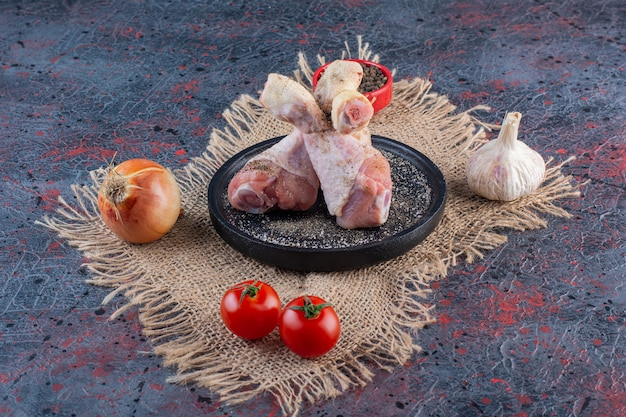 Placa preta de peças de frango cru com legumes na superfície de mármore.