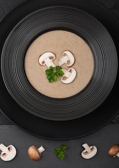 Placa preta do restaurante da sopa cremosa do cogumelo do champignon da castanha no preto com placa de pedra preta e cogumelos frescos.