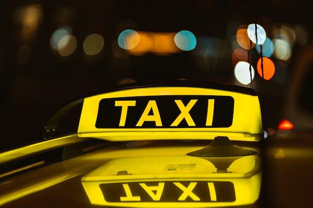 Placa preta e amarela de táxi à noite colocada em cima de um carro
