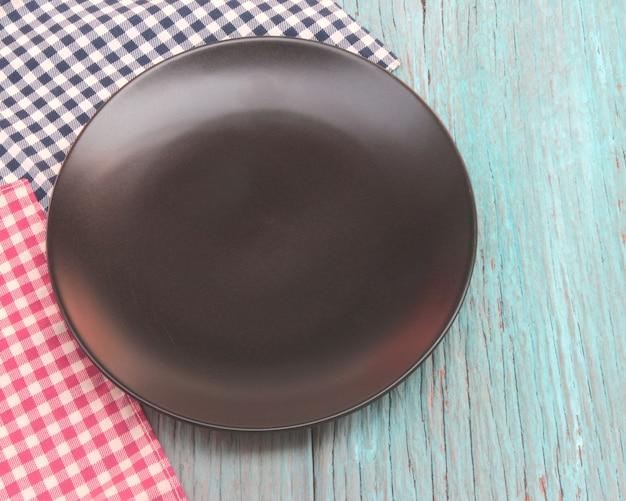 Placa preta na toalha de mesa no fundo da mesa de madeira