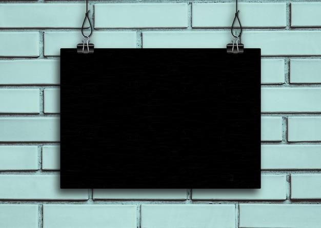 Placa preta no fundo azul da parede de tijolo.