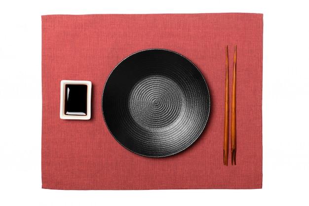 Placa preta redonda vazia com pauzinhos para sushi e molho de soja, guardanapo vermelho. vista superior com copyspace