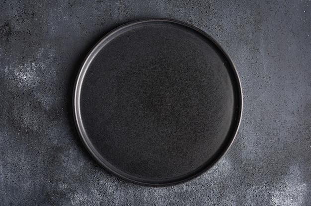 Placa preta redonda vazia na superfície escura