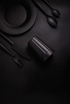 Placa preta, vidro preto e talheres preto sobre um fundo preto, vista superior