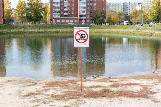 Placa proibindo nadar em um lago perto de edifícios residenciais