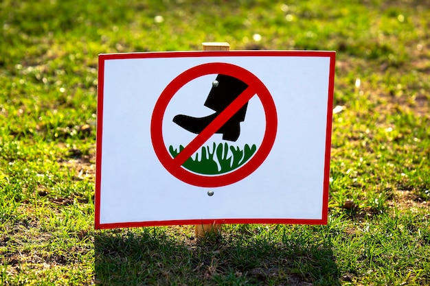 Placa pública proibindo andar na grama