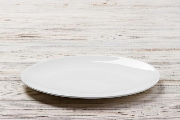 Placa redonda branca sobre fundo branco de mesa de madeira. visão de perspectiva
