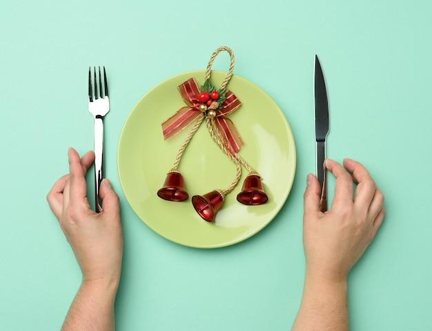 Placa redonda de cerâmica verde com duas mãos segurando uma faca e um garfo