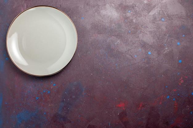 Placa redonda vazia de vidro feita de uma placa cinza na mesa escura.