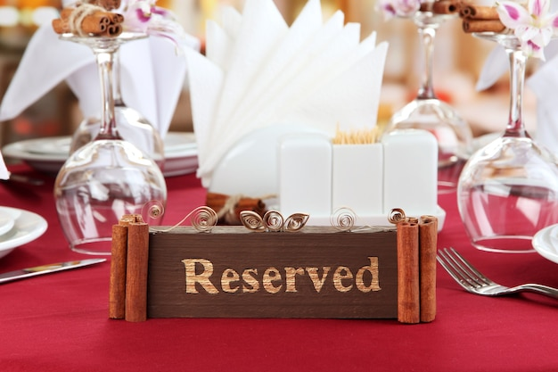 Placa reservada na mesa do restaurante com pratos e copos vazios