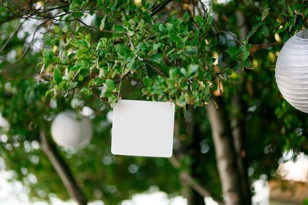 Placa retangular em branco pendurada em uma árvore verde ao lado das lâmpadas