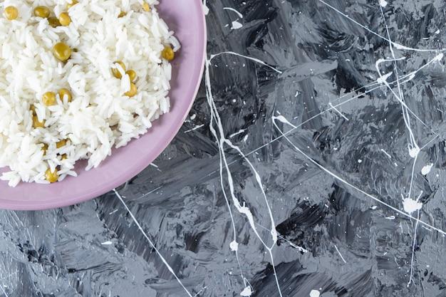 Placa roxa com arroz cozido e ervilhas verdes sobre fundo de mármore.