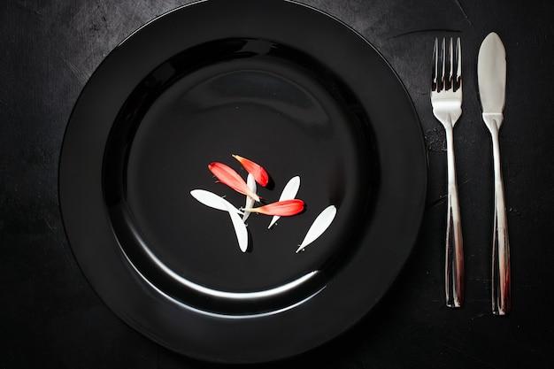 Placa única com garfo e faca em fundo preto. jantar para um. conceito de dieta sarcástica para perda de peso