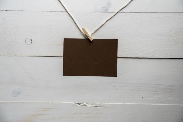 Placa vazia anexada a uma corda com uma parede branca de madeira