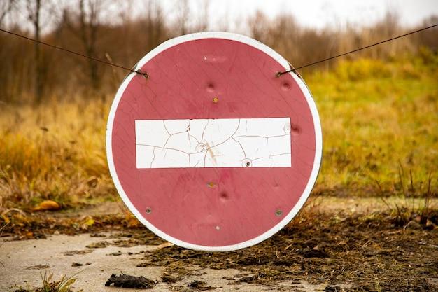Placa velha e enferrujada de nenhuma entrada em uma velha estrada abandonada em um campo