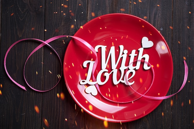 Placa vermelha com letras de madeira com amor em um fundo de madeira, vista superior