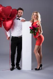 Placa vertical vazia entre homem e mulher