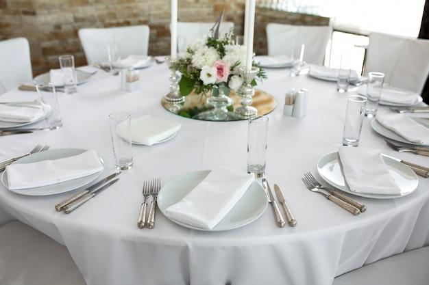 Placas brancas, talheres, toalha de mesa branca e sala branca. mesa de banquete para os hóspedes