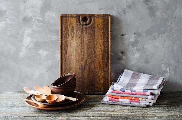 Placas cerâmicas, cutelaria de madeira ou de bambu, placa de corte do vintage e toalhas no interior da cozinha.