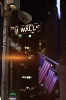 Placas da broadway e de wall street à noite com bandeiras dos eua no fundo, manhattan, nova york