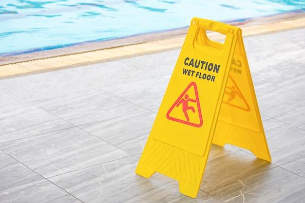 Placas de aviso piso molhado ao lado da piscina.